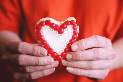 Hands holding heart cookie