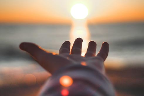 Open hand with sun in background